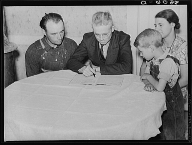County supervisor helping rehabilitation family with account book. Dawson County, Nebraska