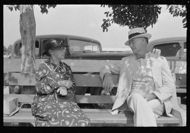 Couple sitting on bench, state fair, Donaldsonville, Louisiana