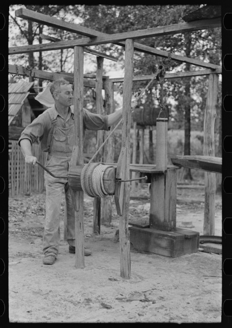Cut-over farmer near Amite, Louisiana, drawing water from well