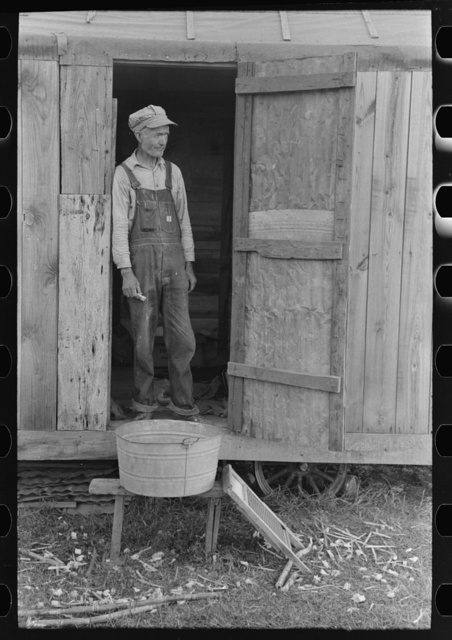 Day laborer standing in doorway of his home in sugarcane fields, near New Iberia, Louisiana