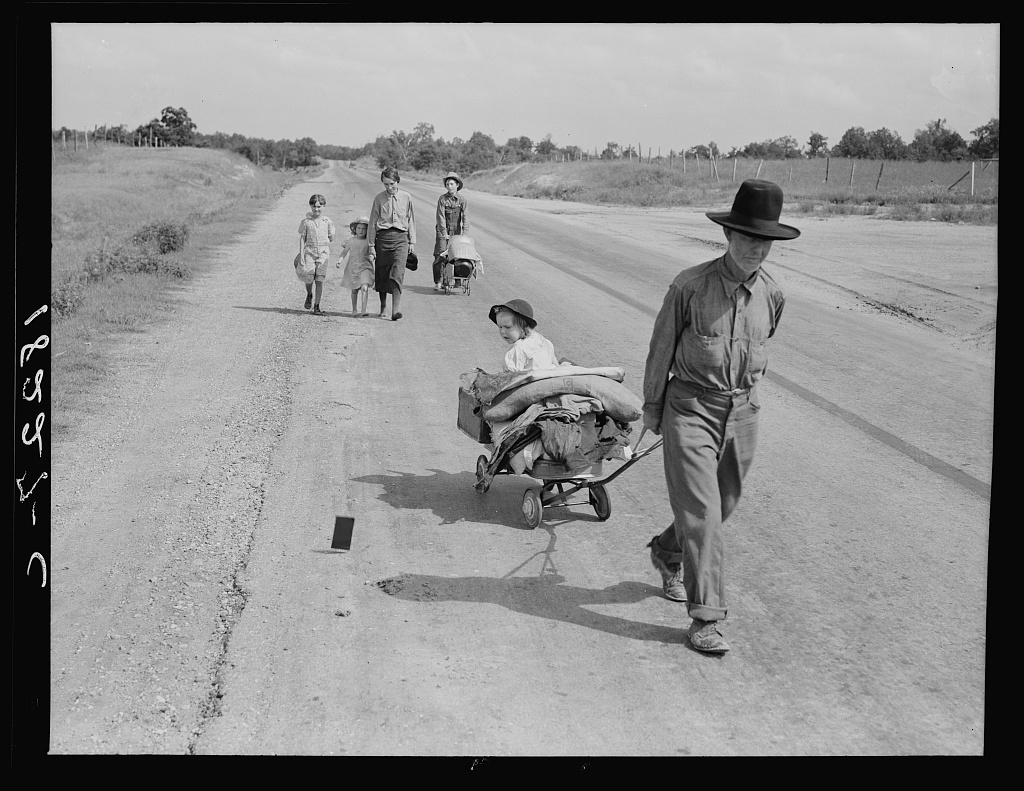 Family walking on highway, five children. Started from Idabel, Oklahoma.  Bound for Krebs, Oklahoma. Pittsburg County, Oklahoma. In 1936 the father farmed on thirds and fourths at Eagleton, McCurtain County, Oklahoma. Was taken sick with pneumonia and lost farm. Unable to get work on Work Prjects Administration and refused county relief in county of fifteen years residence because of temporary residence in another county after his illness