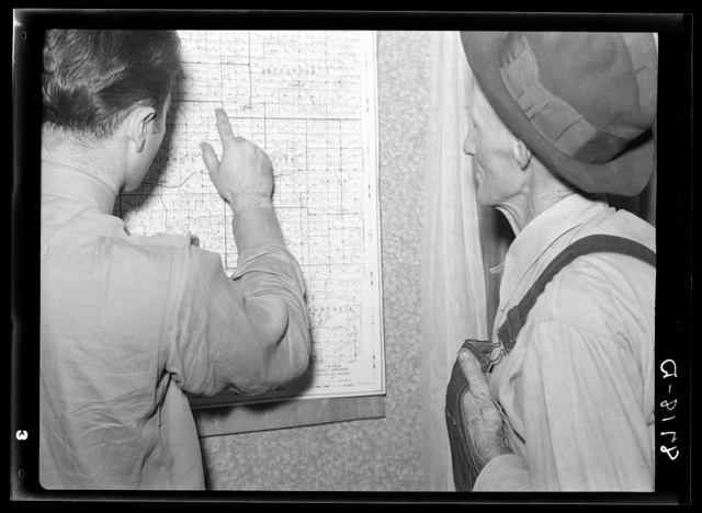 Farm Security Administration county supervisor and rehabilitation applicant examining map of Jefferson County, Kansas
