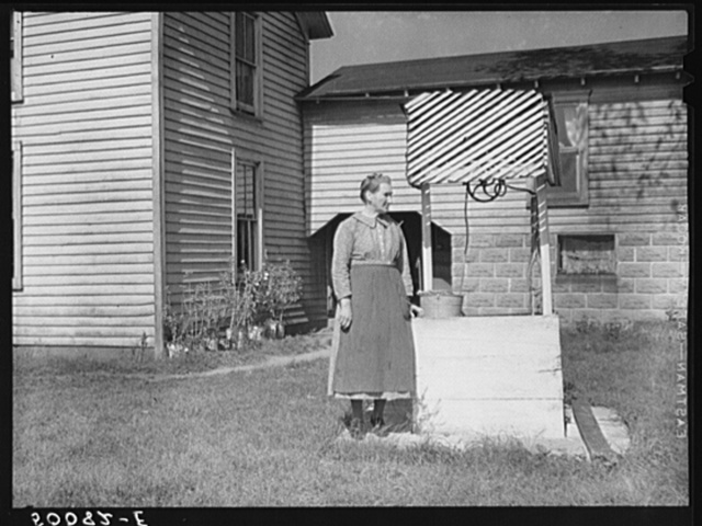 Farm woman standing by well. West Virginia