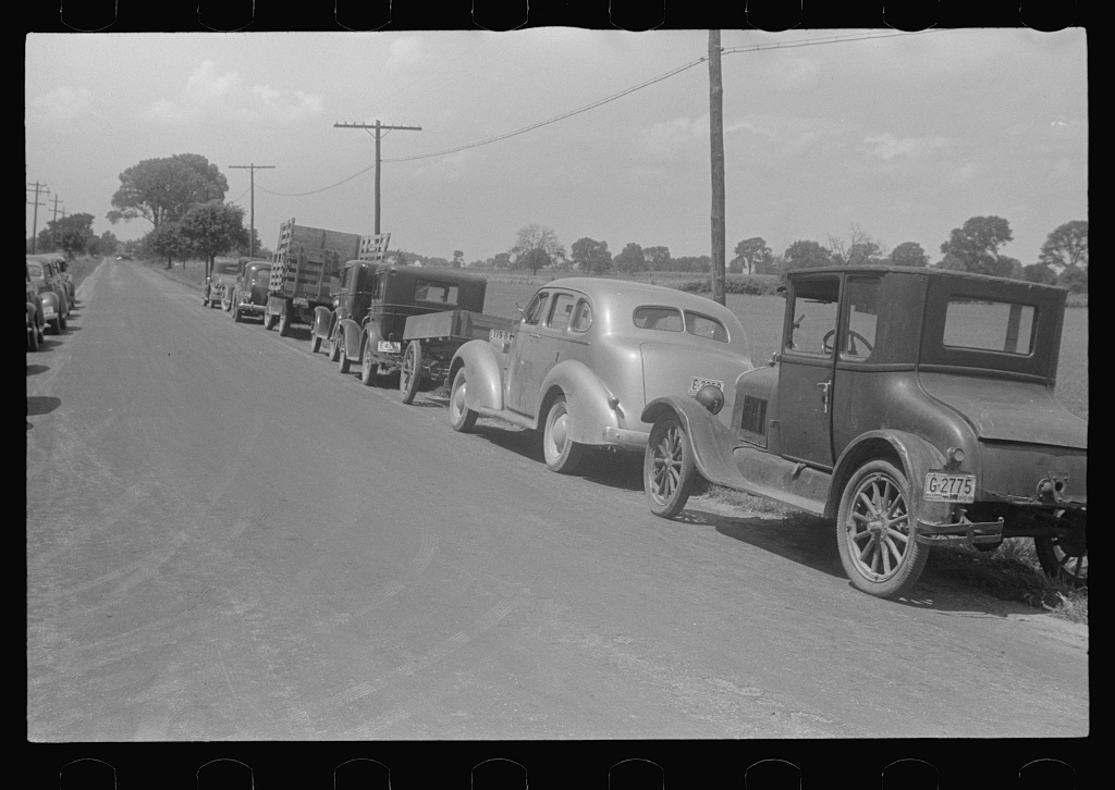 Farmers' cars parked along highway near a public auction, central Ohio