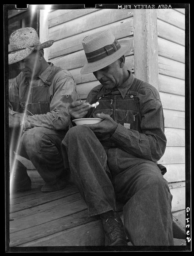 Farmers eating ice cream on the back porch while their wives attended the bimonthly meeting of the Helping Hand society. Gage County, Nebraska