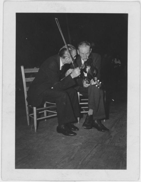 [Fiddling Bill Hensley and his rival for Old Time Fiddlers' Championship, Asa Helton, both seated and talking, holding their fiddles, at the Mountain Music Festival, Asheville, North Carolina]