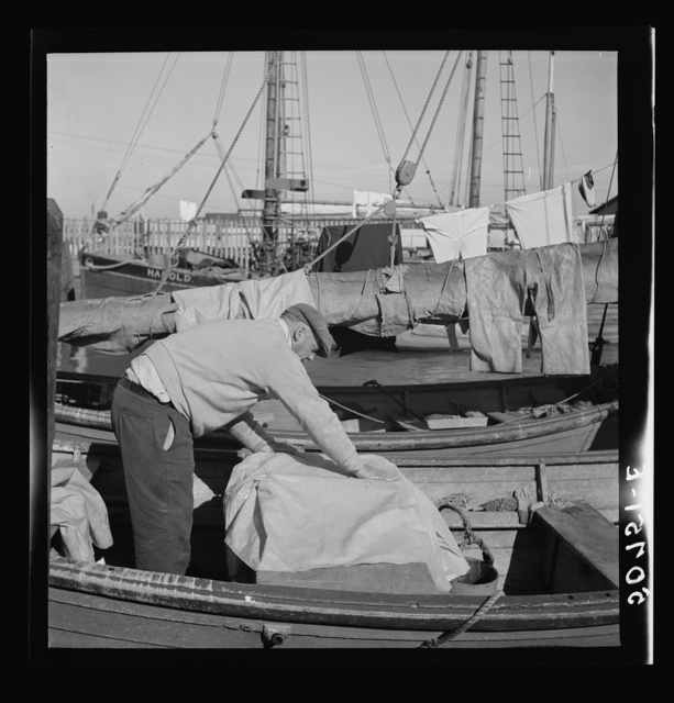 Fisherman oiling waterproof jackets and pants in boat. Christmas Day, Charleston, South Carolina