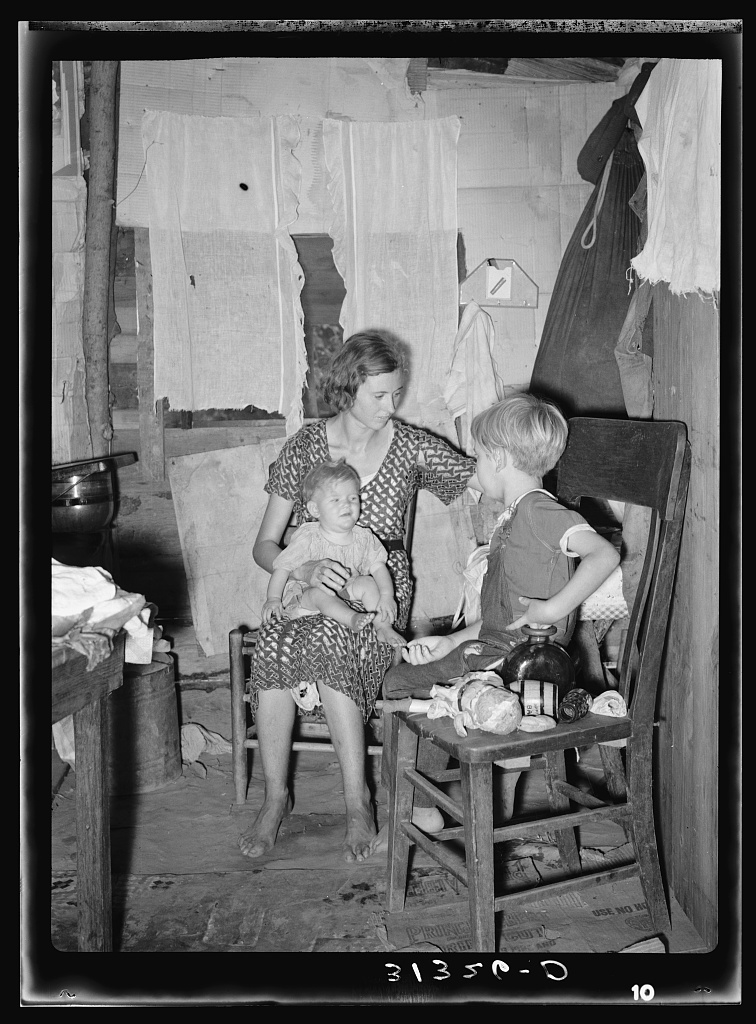 Girl tending fire in shack home. Tin Town, Caruthersville, Missouri