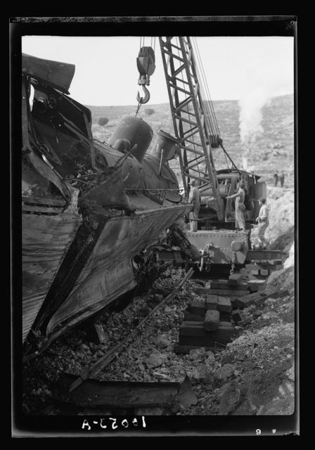 G.O.C. visits overturned locomotive on the Jerusalem Lydda Railroad Line. The locomotive in process of keeling over on to its wheels as the steam-wintch [i.e., winch] chuggs heavily on its weight over double its tested strength