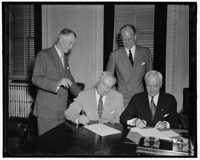 [Group at desk; Sumner Welles, 2nd from right, Cordell Hull, right]