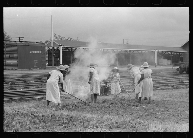 Group of women working along railroad tracks hoeing and burning cut grass, Picayune, Mississippi