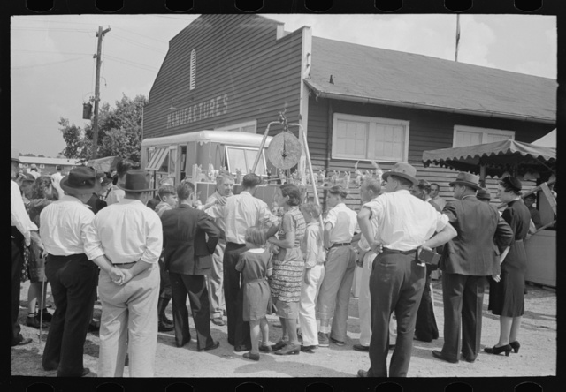 Groups of people standing in front of weighing concession with owner trying to drum up trade, state fair, Donaldsonville, Louisiana