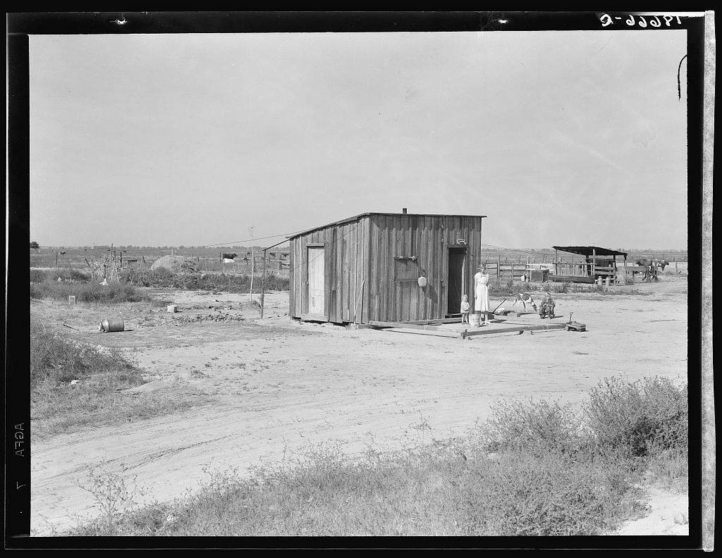 """Home of rural rehabilitation client, Tulare County, California. They bought twenty acres of raw unimproved land with a first payment of fifty dollars which was money saved out of relief budget (August 1936). They received a Farm Security Administration (FSA) loan of seven hundred dollars for stock and equipment. Now they have a one-room shack, seven cows, three sows, and homemade pumping plant, along with ten acres of improved permanent pasture. Cream check approximately thirty dollars per month. Husband also works about ten days a month outside the farm. Husband is twenty-six years old, wife twenty-two, three small children. Been in California five years. """"Piece by piece this place gets put together. One more piece of pipe and our water tank will be finished."""""""