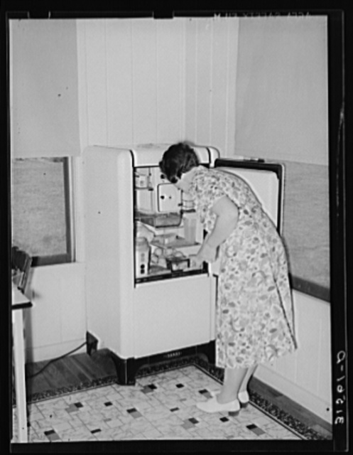 Housewife removing articles from electric refrigerator in farm home. Lake Dick Project, Arkanas