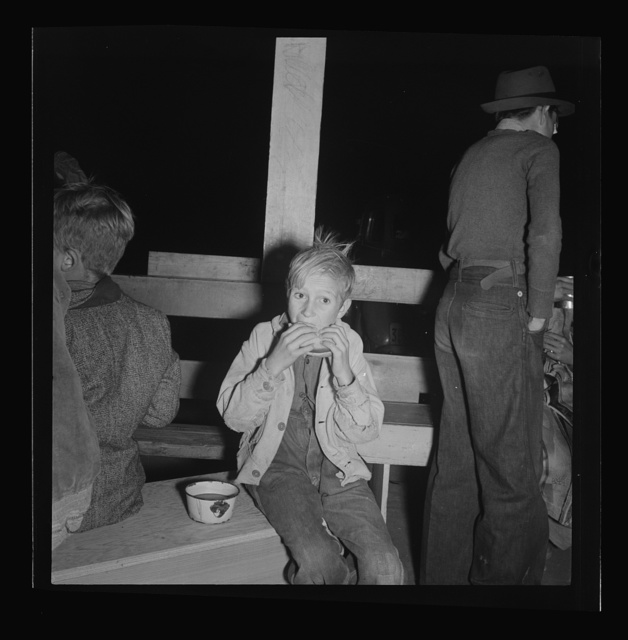 Hungry boy at the Halloween party for migrant workers. Shafter migrant camp, California