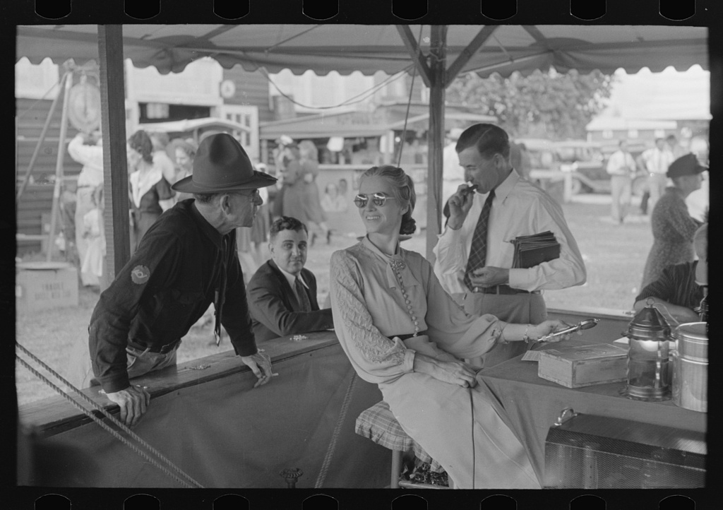 In the game of bingo, an announcement is made by microphone as to the next number coming up. Microphone operator is shown here talking with an old friend who has just arrived. State fair, Donaldsonville, Louisiana