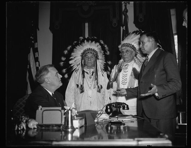 INDIANS VISIT GREAT WHITE FATHER. PRESIDENT ROOSEVELT, SEATED, RECEIVES DRAGS WOLF, LEFT, AND FOOLISH BEAR, RIGHT; WHILE ARTHUR MANDAN, CHIEF OF THE TRIBAL COUNCIL, RIGHT; INTERPRETS FOR THE INDIANS. THE PURPOSE OF THE VISIT WAS TO THANK THE GREAT WHITE FATHER FOR HIS HELP IN RESTORING THE 'SACRED BUNDLE' TO THE WATER BUSTER CLAN OF THE GROS VENTRE TRIBE OF NORTH DAKOTA. A TRIBAL RELIC WHOSE LOSS IN 1907 HAS BEEN FOLLOWED BY SUCH A PERIOD OF DROUGHT AS NONE AMONG THEM CAN REMEMBER. WITH THE RETURN OF THE BUNDLE THE INDIANS THINK THE DROUGHT WILL BE ABOUT OVER