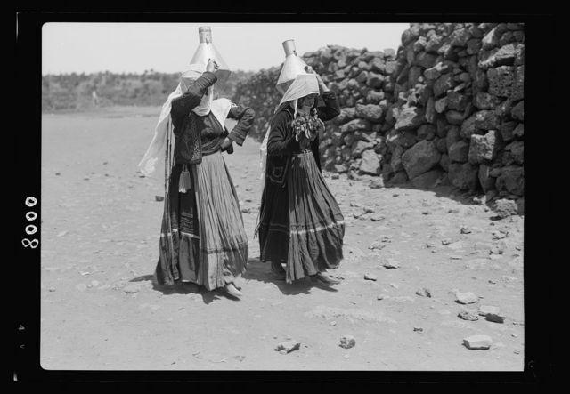Jebel el-Druze & Hauran. Ghureye. Two Druze women with water cans & fine costumes