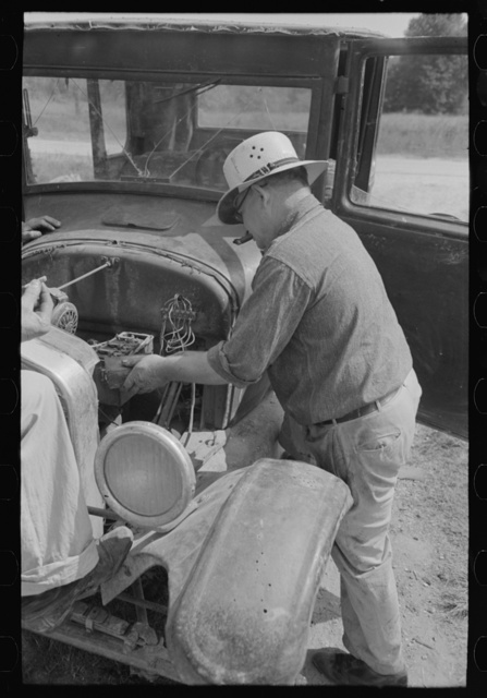 Junkyard owner working on automobile of farmer near Abbeville, Louisiana