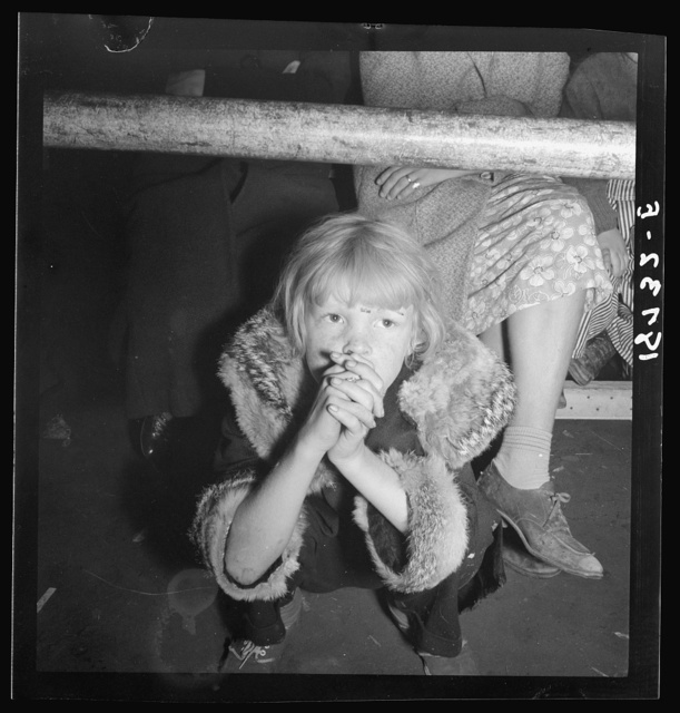 Kern County, California. Undernourished cotton picker's child listening to speeches of organizer at strike meeting to raise wages from seventy-five cents to ninety cents a hundred pounds. Strike unsuccessful