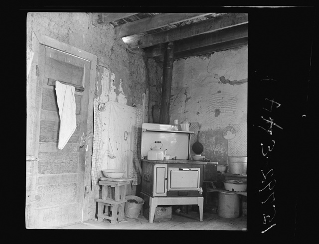"""Kitchen with stove bought last winter from Denver salesman. Great Western Sugar Company's beet sugar workers colony at Hudson, Colorado. The housewife says, """"The man told me it would save its cost in food, but the roof leaks so bad it's getting all rusted up"""" (Notice hole in adobe wall above stove; this stove cost the earnings of about three months' work of all the workers in this family)"""