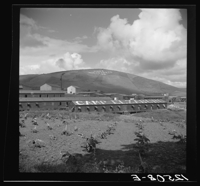 """Labor camp. The inscription on the mountain translated reads: """"P.R.R.A. New Deal"""" (Puerto Rico Resettlement Administration New Deal). Puerto Rico"""