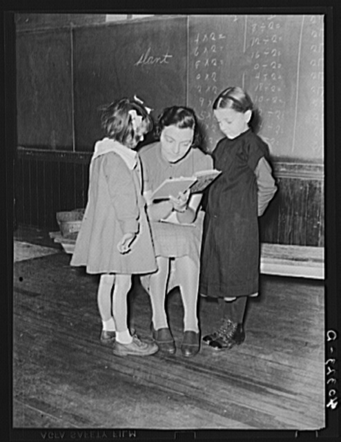 Lancaster County, Pennsylvania. Martha Royer teaching two first graders in her one-room schoolhouse. There are fourteen pupils in the school and the grades run from first to second year high school. The little girl on the right comes from an Amish family