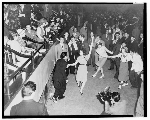 [Large group, mostly men, surrounds couples jitterbug dancing on a dance floor, with a photographer in the foreground and the audience in raised seating on the left] / photo by Alan Fisher.