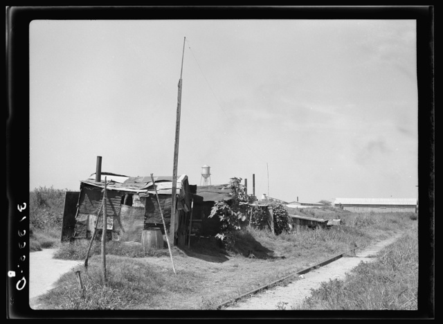 Line of shacks in Tin Town, Caruthersville, Missouri. Industrial plant in the background