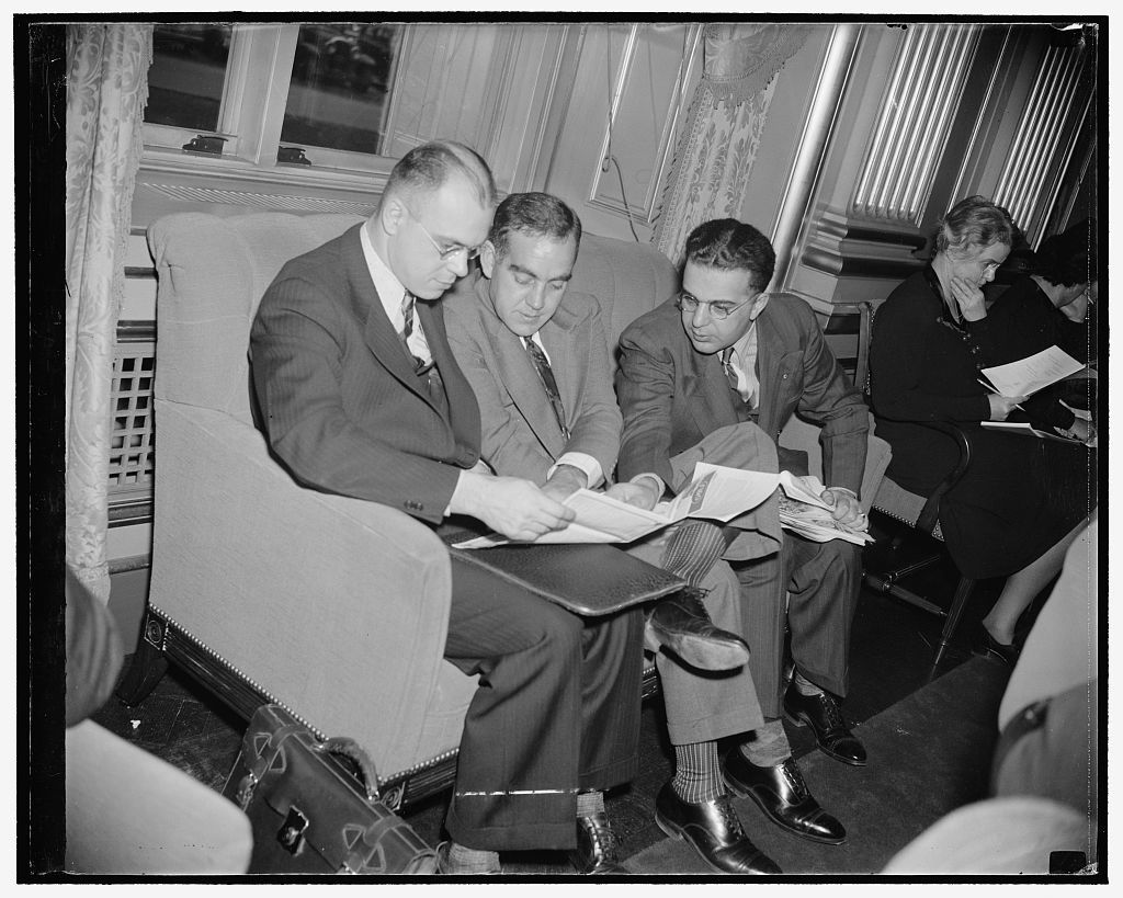 Lloyd J. Haney, President, St. Paul Typographical Union, representing Gov. elect Harold Stassen of Minnesota; E.C. Burris, Helena Montana; B.J. Dorsky, President of the Maine Federation of Labor, from Bangor; all going over a map of Washington with an eye to some sightseeing during breathing spells