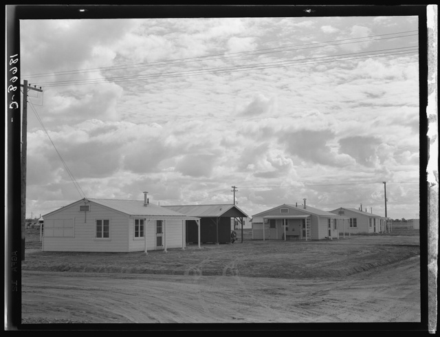 Looking from the camp to adjoining tract where Farm Security Administration (FSA) has just completed forty homes to be occupied by low income workers. These homes represent a first step in stabilization of this group. Rent is eight dollars and twenty cents monthly, which includes gas and electricity. Shafter migrant camp, California