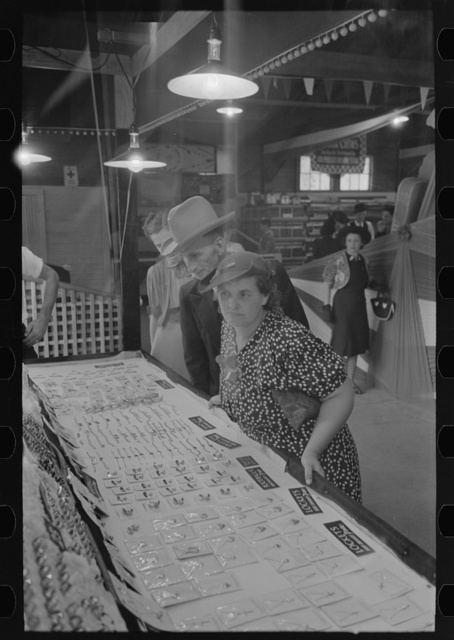 Man and woman looking at display of cheap jewelry, state fair, Donaldsonville, Louisiana