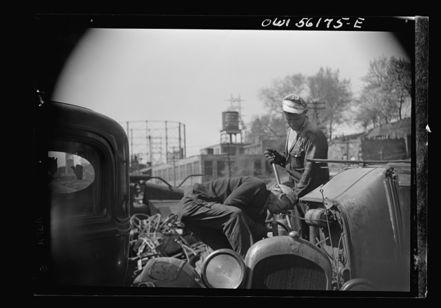 Manayunk, Pennsylvania. Workman at an automobile junkyard on Ridge Avenue