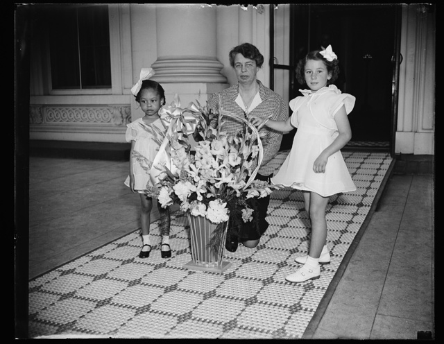 MAY DAY FLOWERS FOR FIRST LADY. WASHINGTON, D.C., MAY 2. MAY DAY, DESIGNATED BY PRESIDENT ROOSEVELT AS CHILD HEALTH DAY, WAS OBSERVED AT THE WHITE HOUSE TODAY WHEN TWO CAPITAL YOUNGSTERS, WARDS OF THE COMMUNITY CHEST, PRESENTED A BASKET OF FLOWERS TO MRS. ROOSEVELT. THE CHILDREN ARE JOAN PERRY, LEFT, 4 YEARS OLD; AND CARLOYN ANN BROWN, 7 YEARS OLD