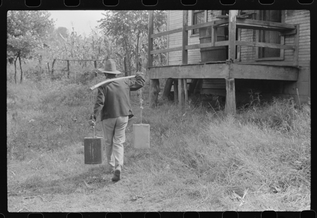 Mexican miner carrying water the way he learned as a boy, from about two miles downhill. Bertha Hill, West Virginia