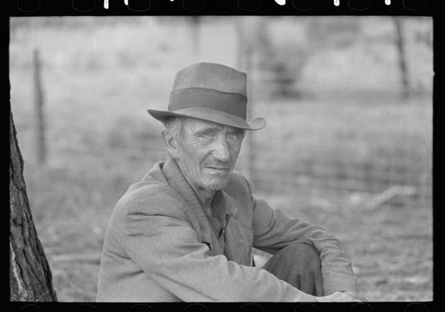 Migrant worker resting along roadside, Hancock County, Mississippi