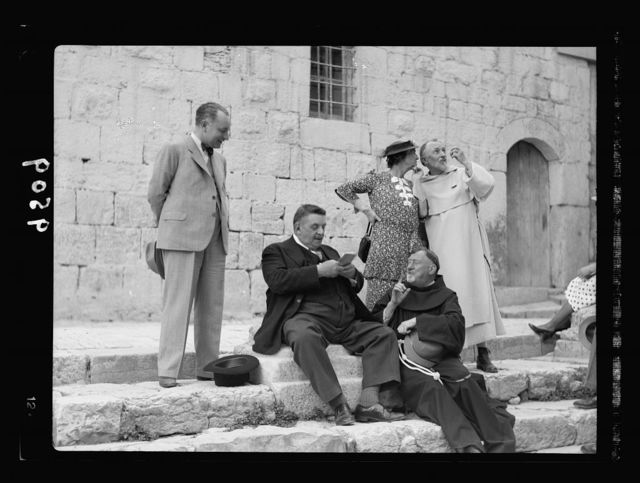 Monsieur & Madame Edouar [i.e., Edouard] Herriot visit to Jerusalem, May 11, 1938. Mr. Herriot & party in front of Ch. [i.e., Church] of Holy Sepulchre showing entrance, Mr. H. seated talking to Fr. Emmanuel Osana