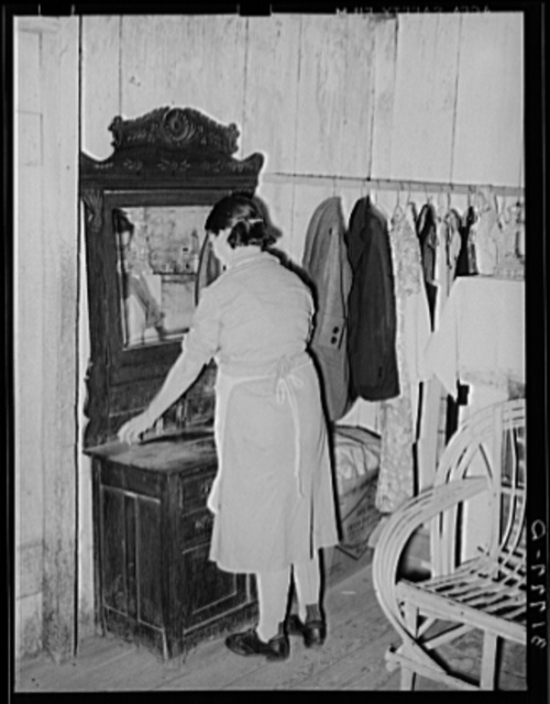 Mrs. M. LaBlanc arranging articles on dresser. Note improvised closet space in this home. La Blancs will be tenant purchase clients