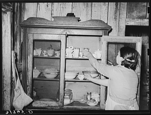 Mrs. M. LaBlanc removing supplies from screened safe. Because of general lack of screens in the house, it is necessary that some means be provided to keep flies from food. Morganza, Louisiana