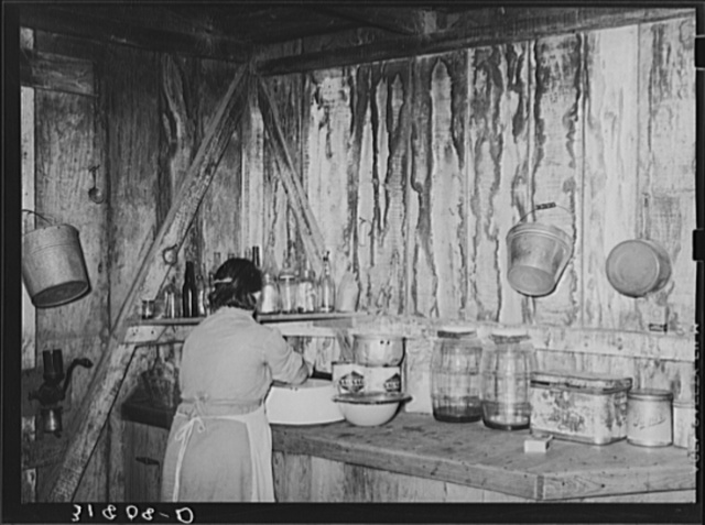 Mrs. M. LaBlanc straightening articles in corner of kitchen in present home. Note the waterstained walls caused by leaking roof. Morganza, Louisiana