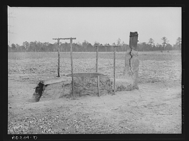 Mud and clay vat for cooking sorghum syrup in front yard of Indians home near Summerville, South Carolina