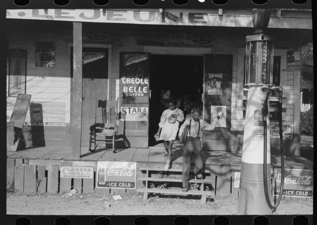 Negro children are coming out of store on way to school. Note lunches which they are carrying in hands. Mix, Louisiana