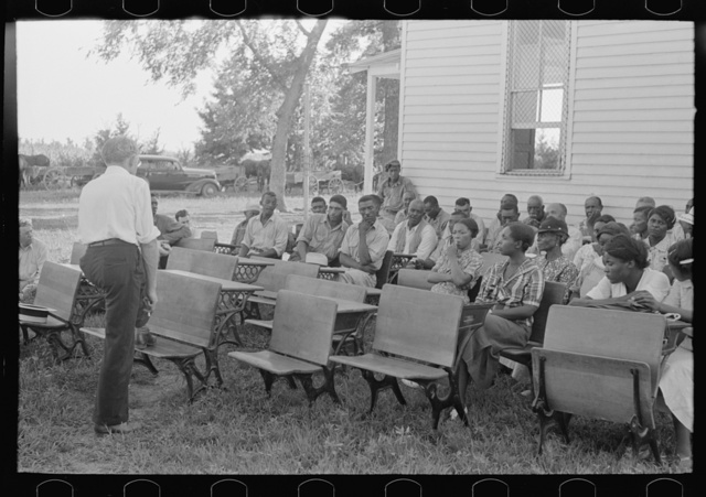 Negro clients and wives listening to speech of project manager, Southeast Missouri Farms