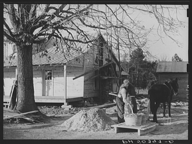 Negro rehabilitation client mixing cement to be used in construction of his new home near Raleigh, North Carolina