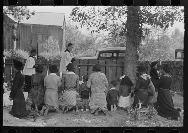Negroes kneeling at graves of relatives, and being blessed by priest with holy water, New Roads, Louisiana