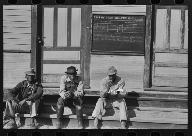 Negroes sitting on foot of the T&P (Texas and Pacific) railroad station, New Roads, Louisiana. Note frequency of train operations
