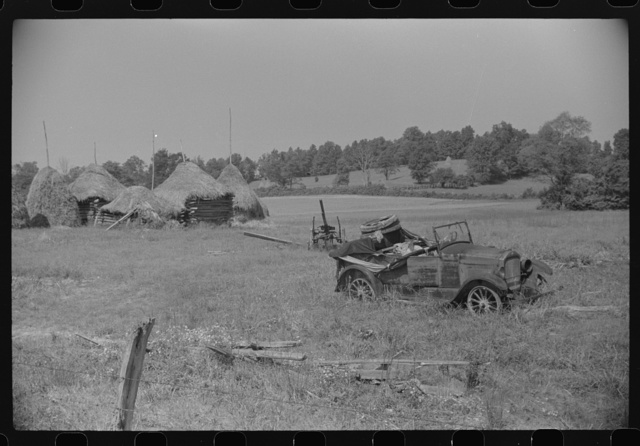Old broken-down car and farm machinery in middle of farmer's field, West Virginia