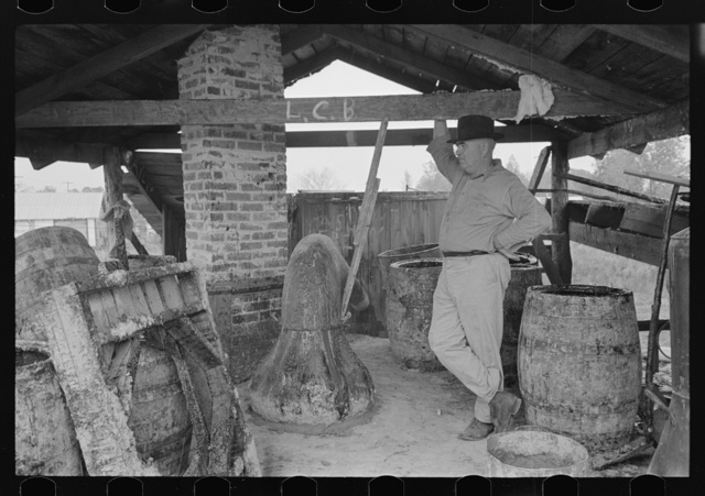 Owner atop his turpentine still. Goosneck runs from the still to the condenser coils where vapors are chilled. State Line, Mississippi