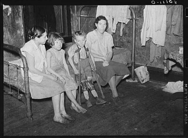 Part of one family living in miner's boarding house. One woman and six children live in one room. Two beds, no water, no heat. Mohegan, West Virginia