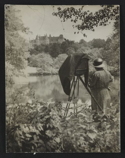 [Photographer Frances Benjamin Johnston standing beside her view camera looking towards the Biltmore Estate mansion in the background]